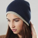 contrast edged beanie hat in acrylic knitted with contrasting off white edge, worn by young woman.