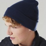 Young man wearing single colour, cuffed beanie hat, double knitted in acrylic. Navy blue.